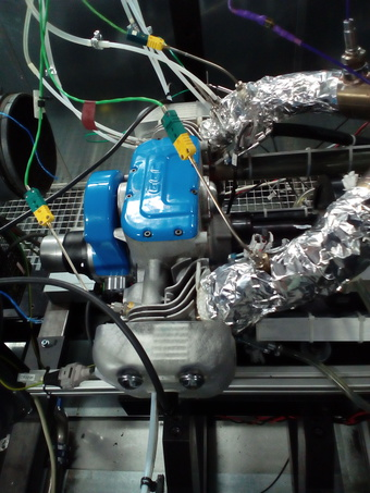Engine of the range extender at the test facilities of ESS Automotive. The blue cover conceals the central section of the engine; in the foreground are the front cyl